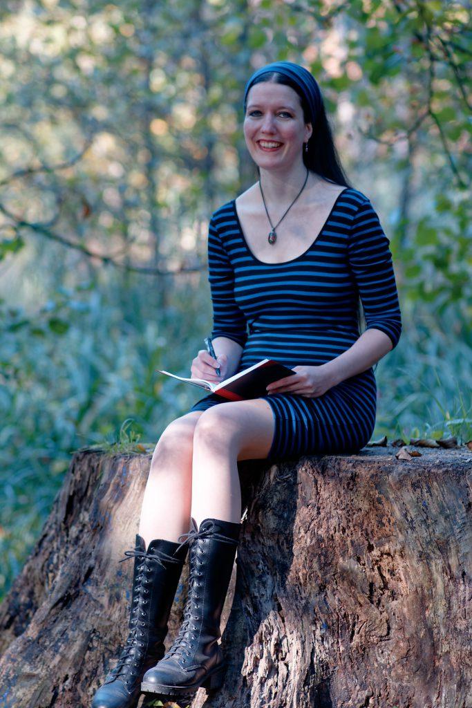 Lächelnde Frau im blau-schwarzen KLeid, die mit Stift und Notizbuch auf einem Baumstumpf sitzt | Klopfecke - PR-, Web- und Marketing-Texte mit Geist