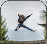 Frau mit Rucksack beim Luftsprung im Wald vorm Meer | Die Texterin aus der Klopfecke sagt vielen Dank 2